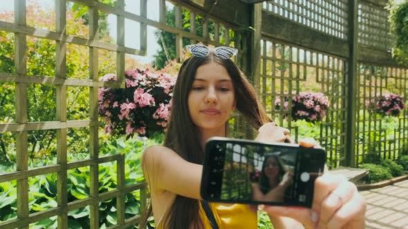 Thumbnail for Ein Mädchen mit einem Telefon im Park macht ein Foto
