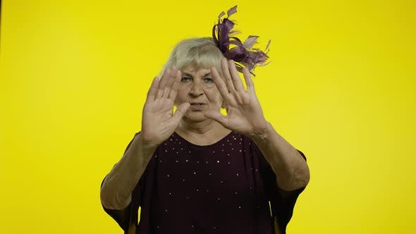 Annoyed Irritated Mature Old Woman Covering Ears and Gesturing No, Avoiding Advice, Ignoring Noise
