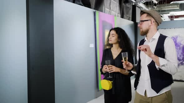 Man Is Performing Excursion in Art Gallery for Pretty Brunette Woman