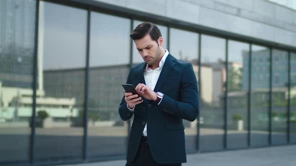 Thumbnail for Closeup Businessman Reading Bad News at Street. Businessman Using Smartphone