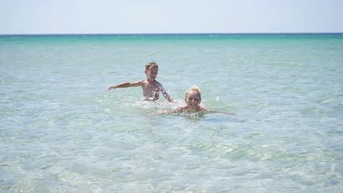 Happy Child Splashes Water on His Mother in the Sea