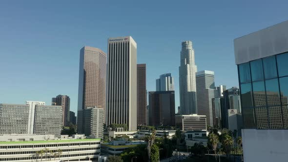 Thumbnail for AERIAL: Reveal of Downtown Los Angeles, California Skyline Behind Building with Glass Windows at
