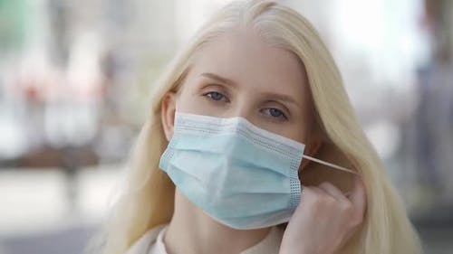 An Attractive Young Woman Takes Off Her Medical Mask and Smiles