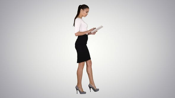 Thumbnail for Attractive businesswoman using a digital tablet while walking