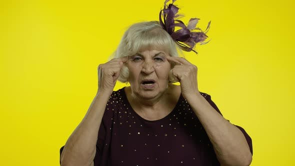 Thumbnail for Displeased Annoyed Senior Old Woman Showing Stupid Gesture, Elderly Grandma on Yellow Background