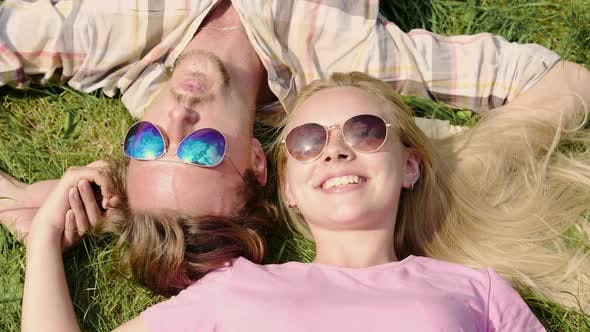 Thumbnail for Happy Young Couple Enjoying Weekend, Lying on Lawn and Talking, Summertime