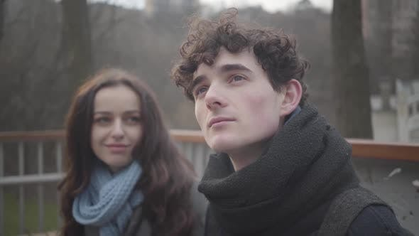 Thumbnail for Close-up of Young Curly-haired Caucasian Man Looking Up and Smiling As Girlfriend Putting Head on