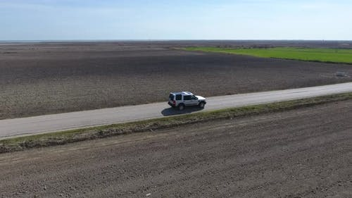 Car Going on The Road Between Green and Brown Fields