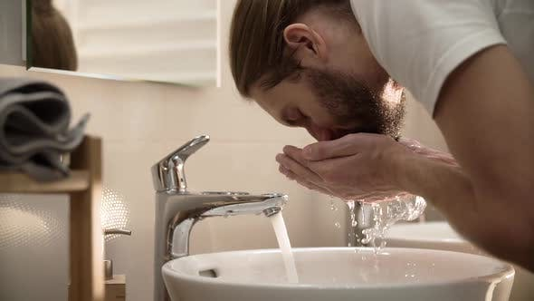 Morning Hygiene. Man Washing Face With Clean Water At Bathroom
