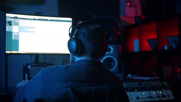 Cover Image for A Man Sound Engineer in Headphones Working in the Neon Sound Recording Studio