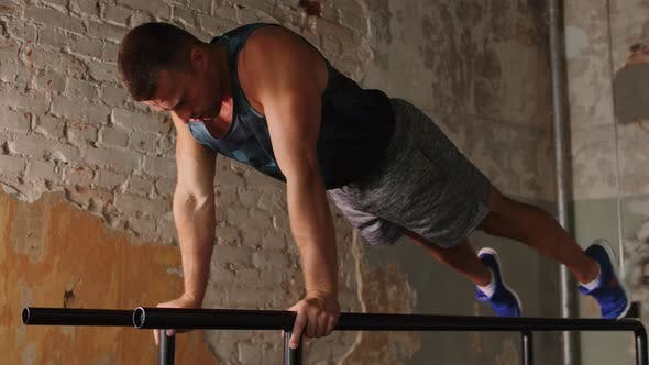 Thumbnail for Man Doing Push-ups on Parallel Bars in Gym