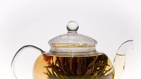 Thumbnail for Closeup. Teapot with a Blossoming Red Flower Green Chinese Tea