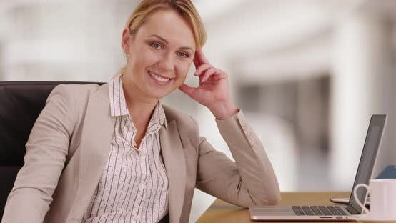 Thumbnail for Businesswoman sitting at desk smiling at camera