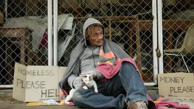 Homeless holding and playing with cat