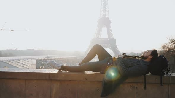 Relaxed Happy Male Tourist Lying Down with Eyes Closed at Amazing Sunset Eiffel Tower View in Paris