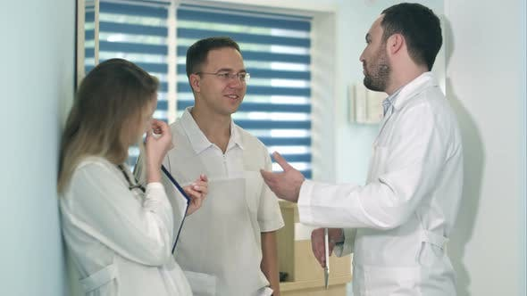 Thumbnail for Male Doctor Holding Tablet Talking To Two Others Doctors in the Hospital Hall