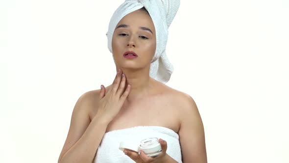 Thumbnail for Portrait of Young Woman in White Towel on Her Head Applying a Cream on Her Previously Cleansed Face