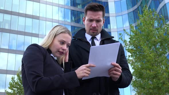 Thumbnail for A Businessman and a Businesswoman Discuss Papers in Front of an Office Building - View From Below