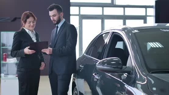 Thumbnail for Positive Successful Caucasian Woman Signing Sale and Purchase Agreement in Car Dealership