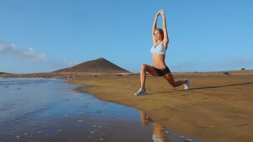 Yoga Retreat and Training - Woman in Yoga Pose at Beach at Sunrise