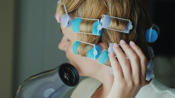 Thumbnail for Woman with Curlers on Her Head Dries Hair with a Hairdryer