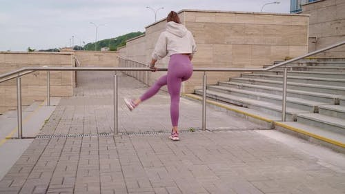 Woman is Training Her Body for Good Looking Waving Legs Outdoors