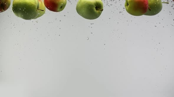 Cover Image for Ripe Apples Green and Yellow Red Under Water with Splashes and Air Drops on White Background