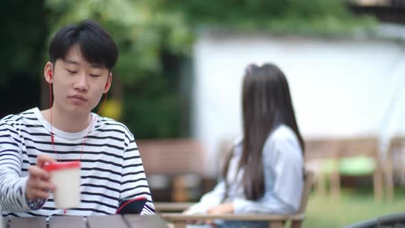 Cover Image for Asian Teenager Listening to Music and Messaging on Phone at Cafe Table