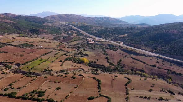 Panoramic Aerial View of Mountain Valley with Farmlands and Road