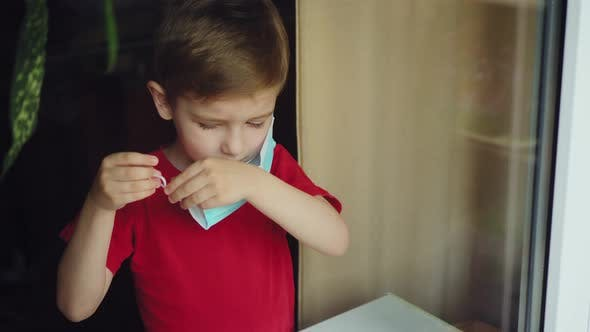 the Child Puts on a Mask Near the Window