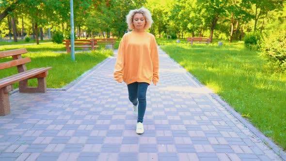 Thumbnail for Unhappy Girl in Yellow Sweater Walking in Park