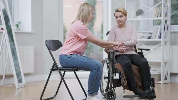 Plan large de triste jeune femme handicapée en fauteuil roulant et ami de soutien tenant la main