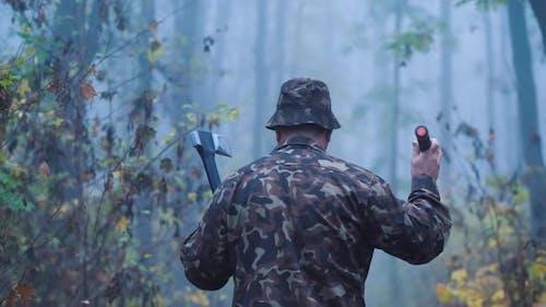 Rückansicht von Brutal Mann mit einer Axt und eine Taschenlampe geht durch den Wald