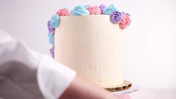 Thumbnail for Baker piping pastel color buttercream rosettes on a white cake to make a unicorn cake.