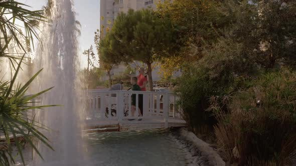 Thumbnail for Mother with Children Walking in Hotel Garden with Fountains