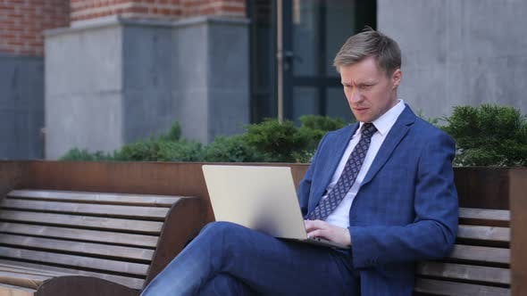 Thumbnail for Businessman Working On Laptop Sitting Outside Office