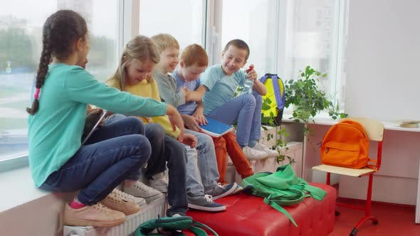 Primary School Teacher Giving Workbooks to Kids