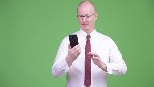 Thumbnail for Happy Mature Bald Businessman Using Phone and Getting Good News