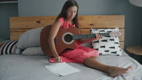 Thumbnail for Young woman with guitar on the bad writes a new song