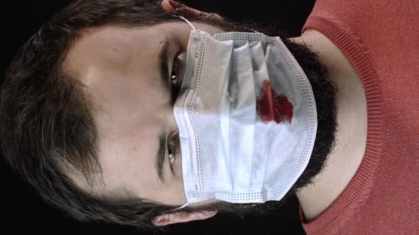 Vertikaler Schuss Kranker Mann in medizinischer Maske mit Blut drauf setzt neue Maske auf