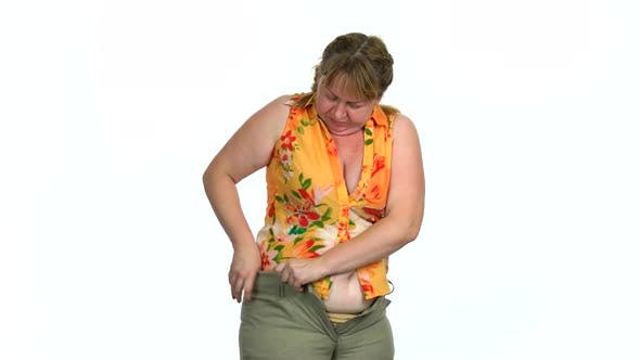 Woman Struggling To Zip Tight Pants