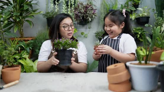 Mother teaching daughter to plant trees