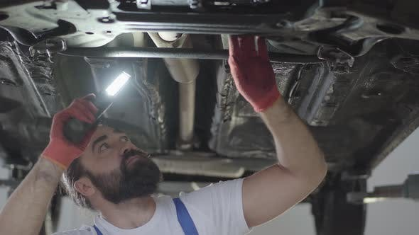 Thumbnail for Bearded Car Mechanic Inspecting Suspension or Brakes in Car with Lamp of Lifted Automobile at Repair