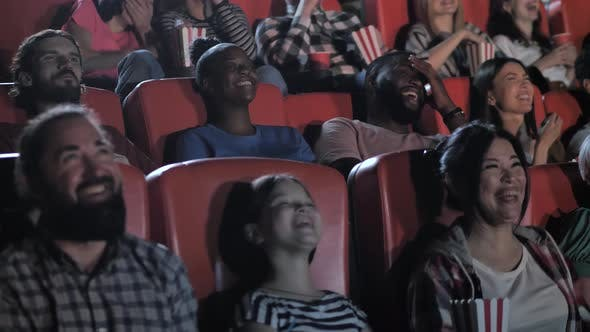 Joyful Spectators Watching Comedy in Movie Theater