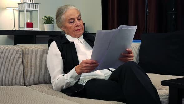 Thumbnail for Old Caucasian Woman Reads Some Documents in Living Room