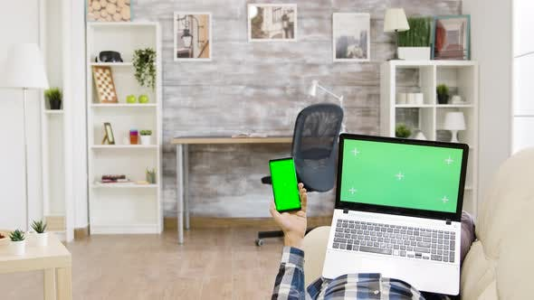Thumbnail for Man Lying on the Sofa Holding a Green Screen Laptop and Smartphone in His Hands