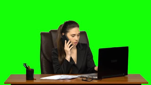 Cover Image for Girl Working on a Laptop Then Answers the Call By Mobile Phone. Green Screen