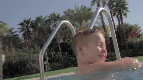 Joyful kid splashing water in swimming pool outdoor