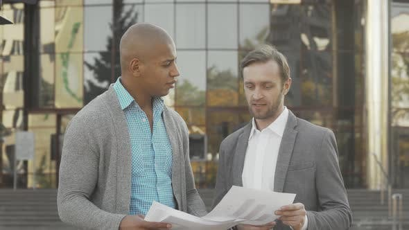 Thumbnail for Two Businessmen Examining Documents in Front of Business Building