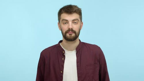 Handsome Caucasian Man with Beard Looking at Camera and Playing with Thick Eyebrows Hinting on